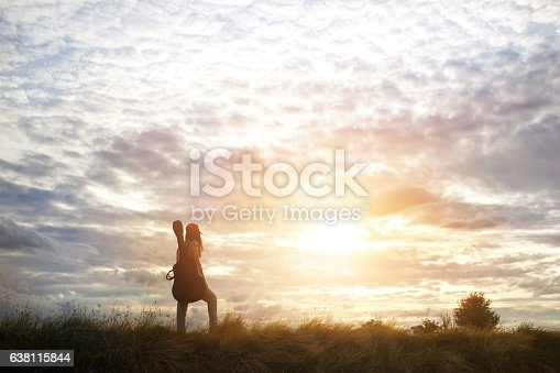istock Woman carrying a guitar on her shoulder, countryside road 638115844