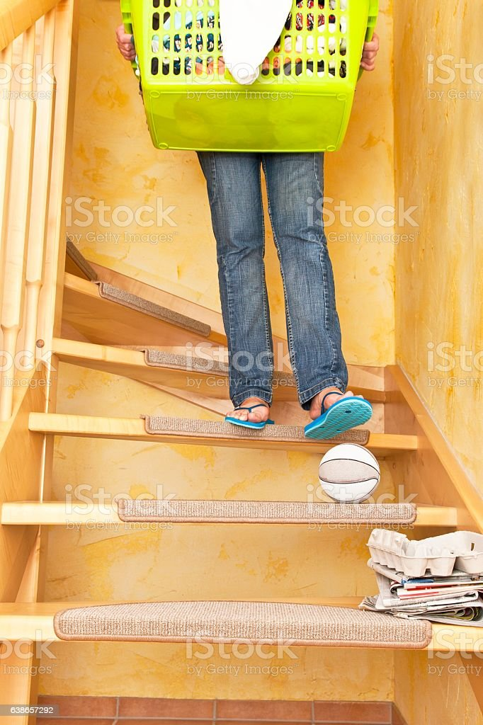 Woman carrying a laundry basket and stepping on a basketball stock photo