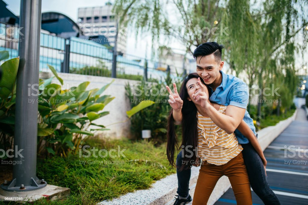 Woman carrying a man on her back royalty-free stock photo