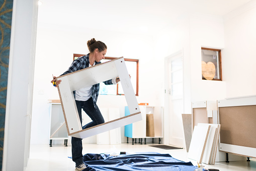 Woman carrying a partial assembled kitchen unit to a workspace