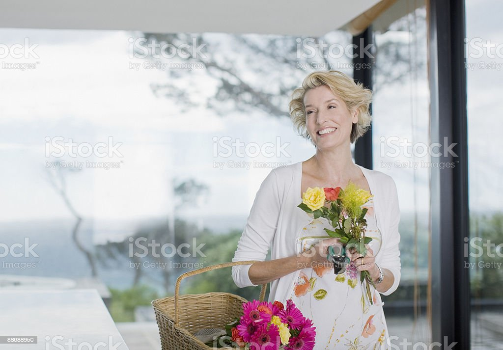 Woman carrying basket of flowers royalty-free stock photo