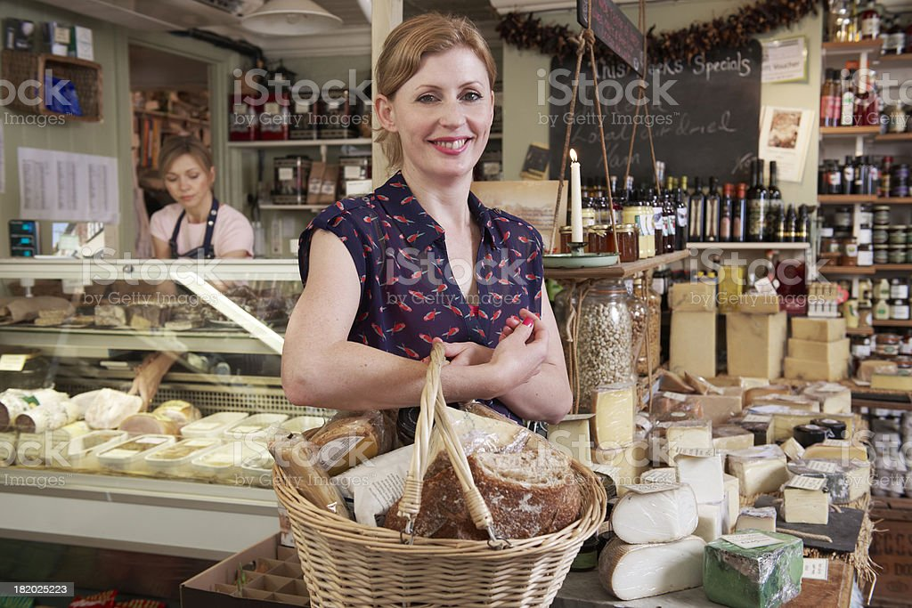 Woman Carrying Basket Of Groceries In Delicatessen stock photo