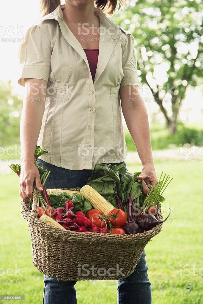 Woman carrying basket of produce stock photo