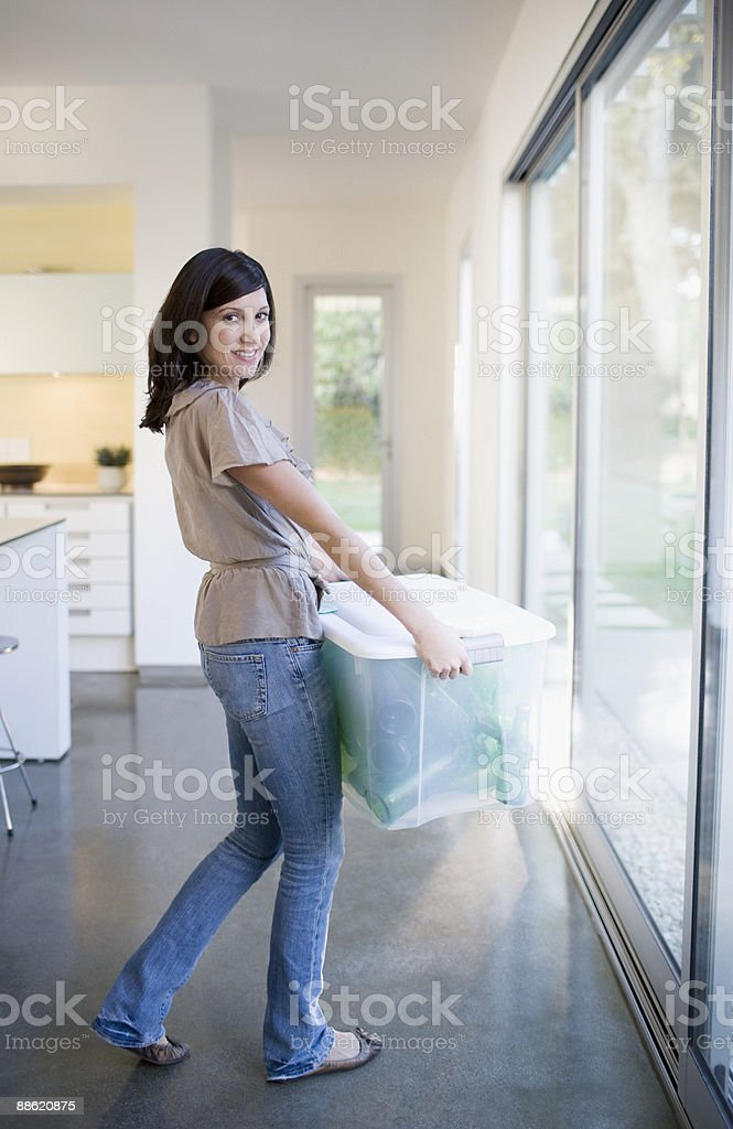 Woman carrying bin of glass bottles stock photo