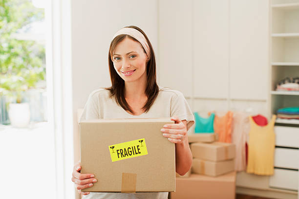 woman carrying box with fragile sticker into new house - fragile stock photos and pictures