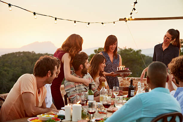 Woman carrying cake by friends at table Happy woman carrying cake by friends at table during social gathering happy birthday stock pictures, royalty-free photos & images