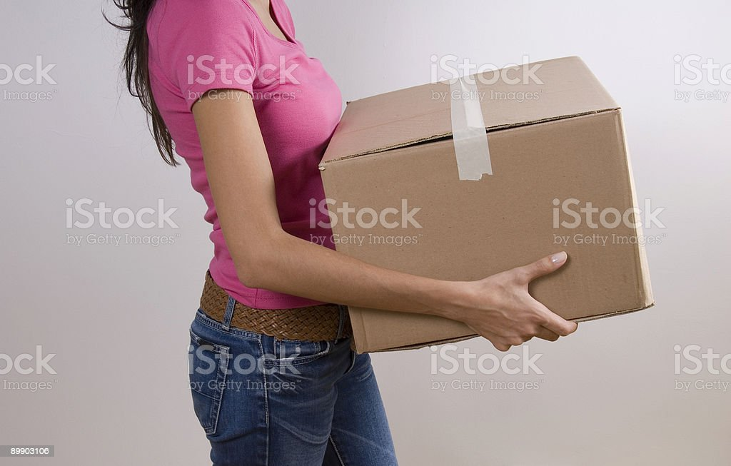Woman carrying cardboard box, side view royalty-free stock photo
