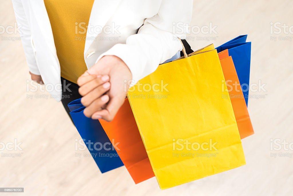 Woman carrying colorful paper shopping bags royalty-free stock photo