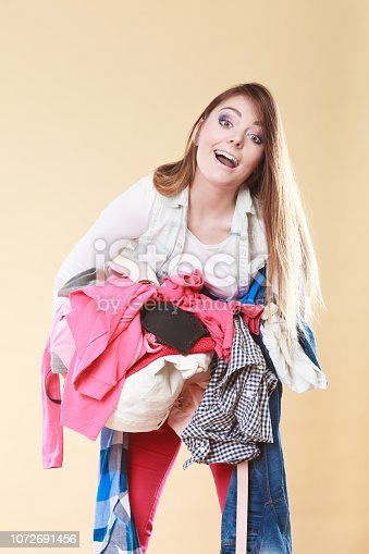 460589747istockphoto Woman carrying dirty laundry clothes. 1072691456