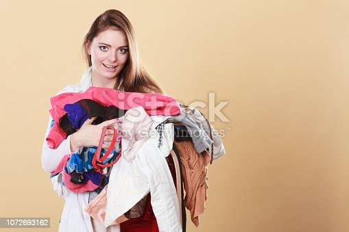 460589747istockphoto Woman carrying dirty laundry clothes. 1072693162