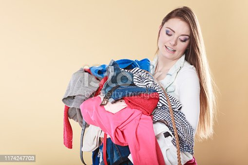 460589747istockphoto Woman carrying dirty laundry clothes. 1174247703