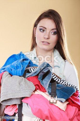 460589747istockphoto Woman carrying dirty laundry clothes. 1174249563