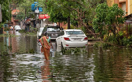 Kolkata, West Bengal, India, May 20, 2020: Woman carrying essential drinking water through water logged city street after massive cyclonic storm Amphan strike at Kolkata, India