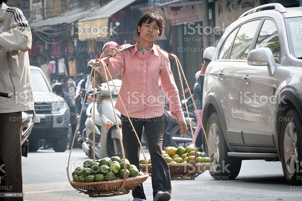 Woman Carrying Fruit To Market In Hanoi, Vietnam royalty-free stock photo