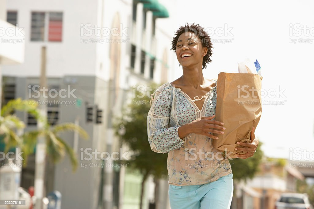 Woman Carrying Grocery Bag While Walking On Street stock photo