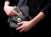 A close-up of a woman holding a handgun in a purse.