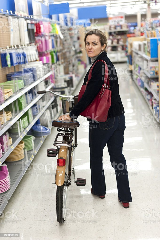 Woman carrying her bike inside a shop royalty-free stock photo