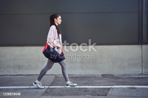 Female running athlete leaving her workout place after a hard session of training