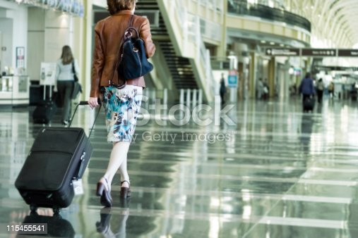Woman toting luggage for a trip.