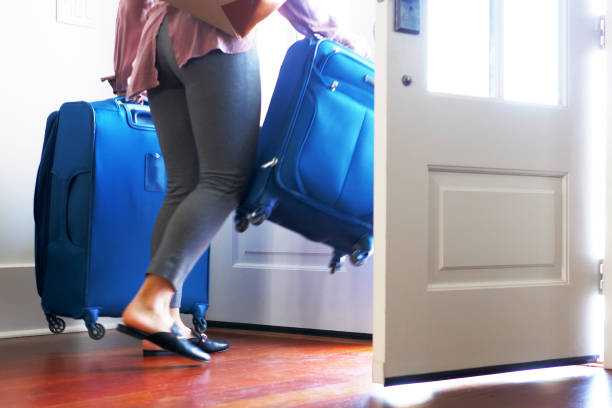 Woman carrying luggage out front door of home. stock photo