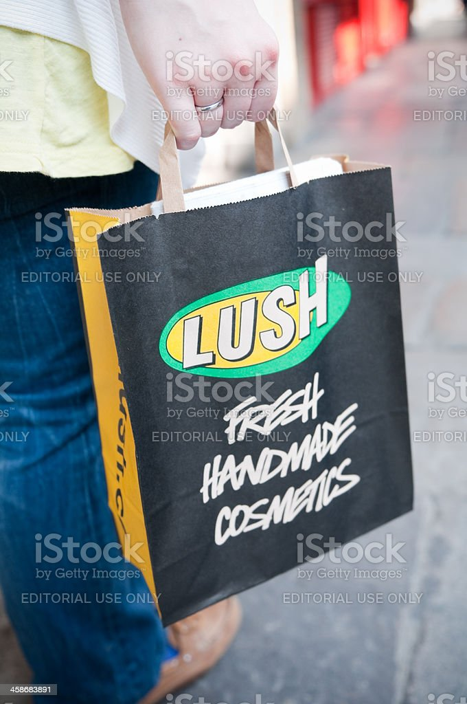 Woman carrying Lush cosmetics bag in London, UK royalty-free stock photo