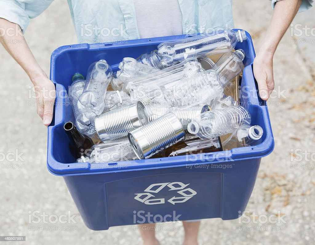 Woman carrying recycle bin stock photo