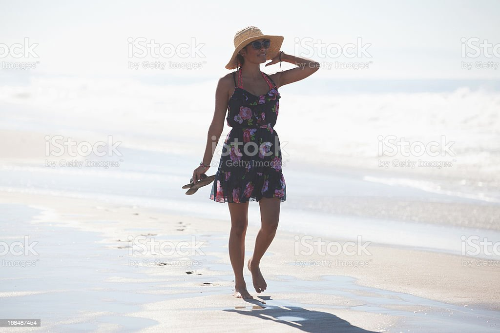 Woman carrying sandals on beach royalty-free stock photo