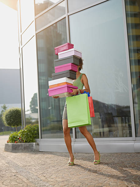 woman carrying shoe boxes - large group of objects stock photos and pictures