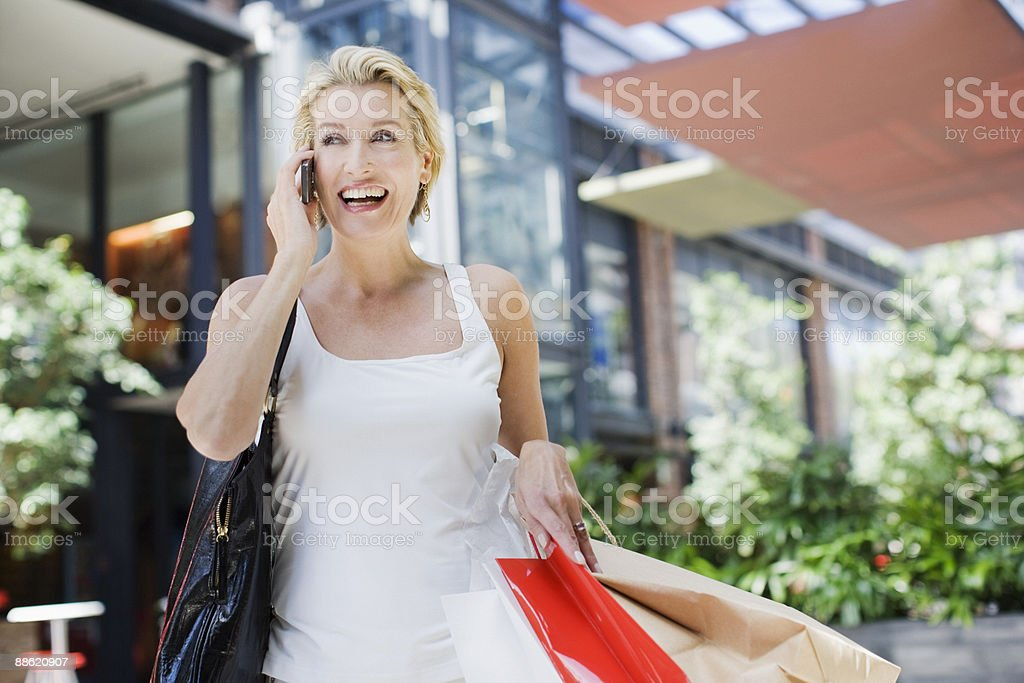 Woman carrying shopping bags and talking on cell phone royalty-free stock photo