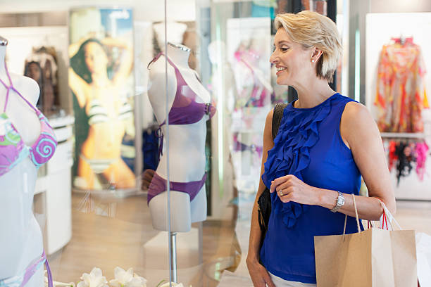 woman carrying shopping bags in mall - older women bikini stock pictures, royalty-free photos & images