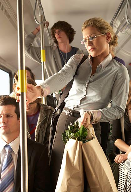Woman carrying shopping bags on busy bus stock photo