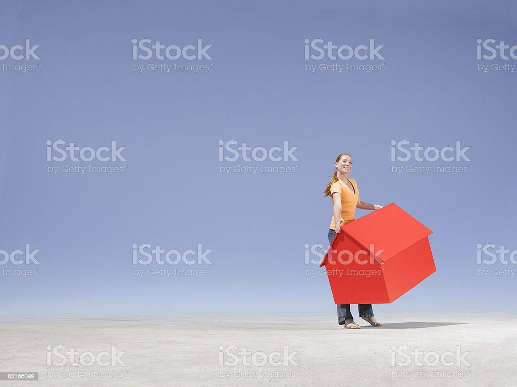 Donna portare piccola casa modello nel deserto foto stock royalty-free
