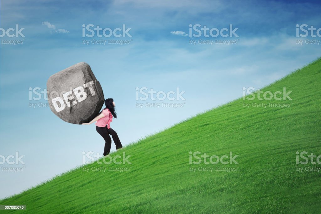 Woman carrying stone on hill stock photo
