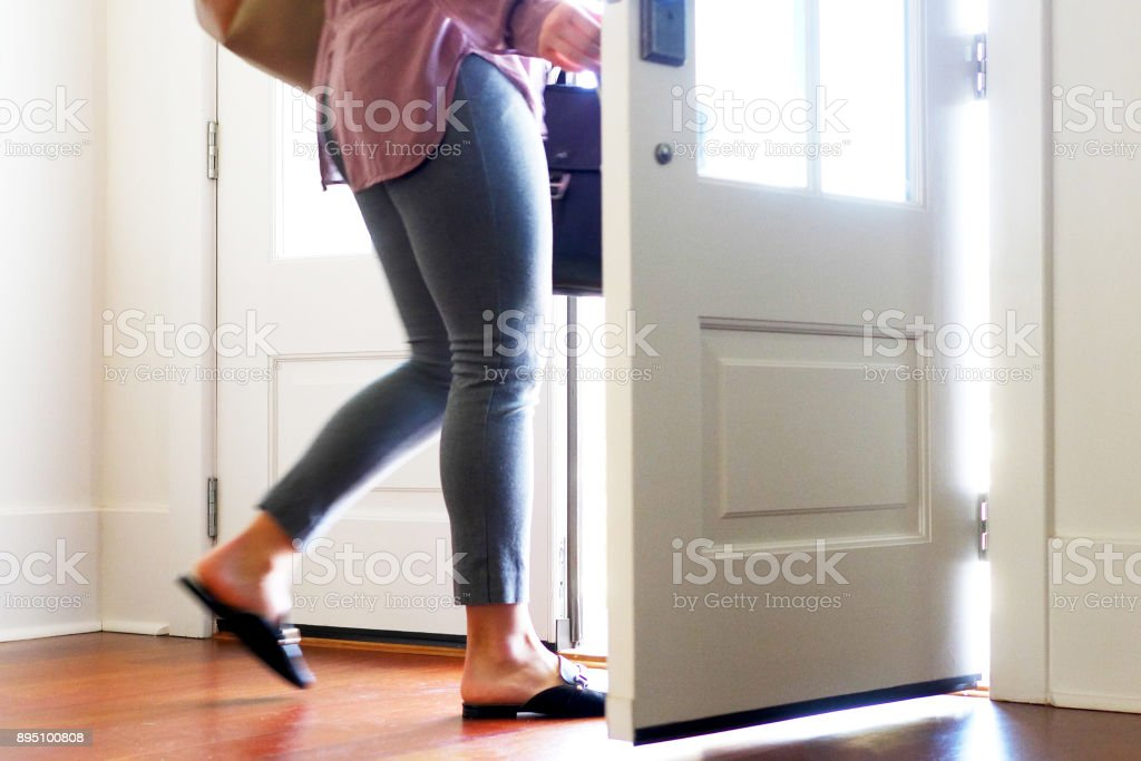 Woman carrying walking out from door. stock photo