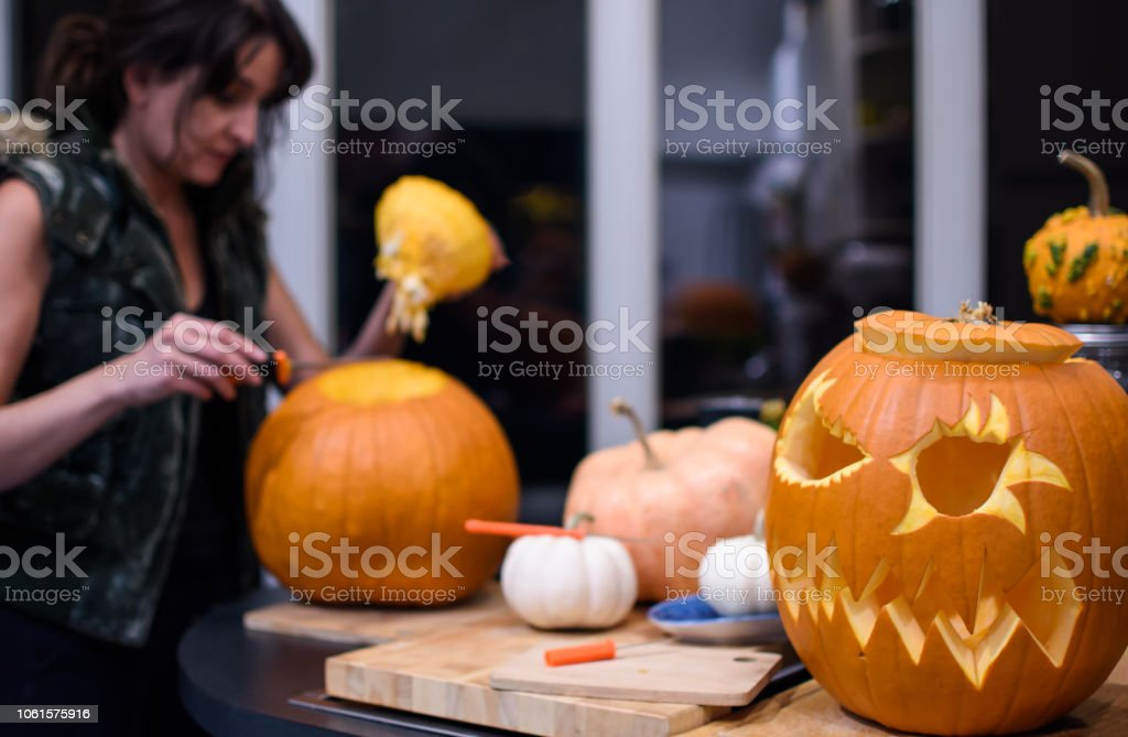 Woman carving Halloween pumpkin at home with cute dog Jack o'lantern stock photo