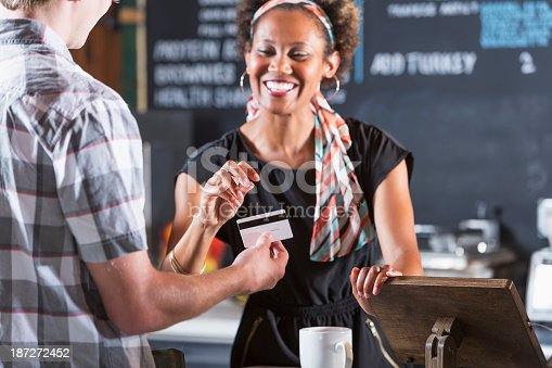 istock Woman cashier taking payment from customer 187272452