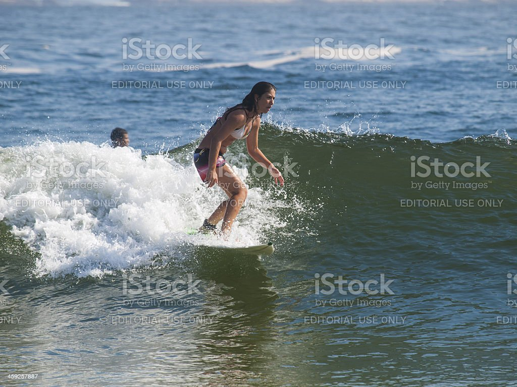 Woman catches a wave at Ipanema Beach in Rio, Brazil royalty-free stock photo