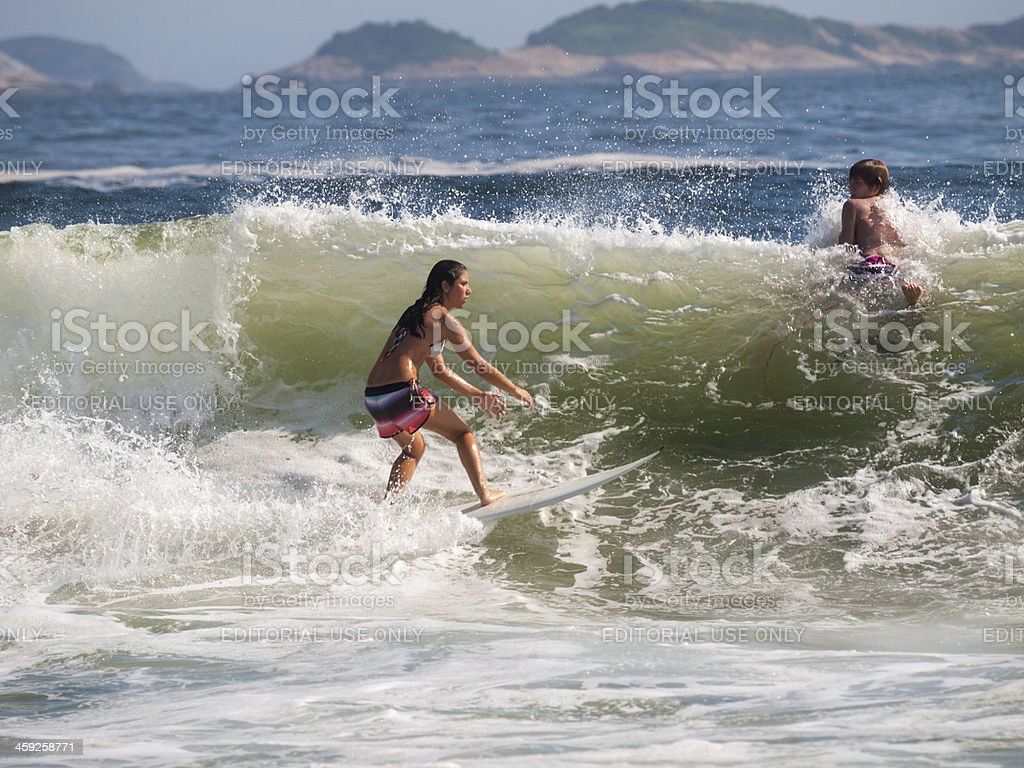 Woman catches a wave at Ipanema Beach in Rio, Brazil stock photo