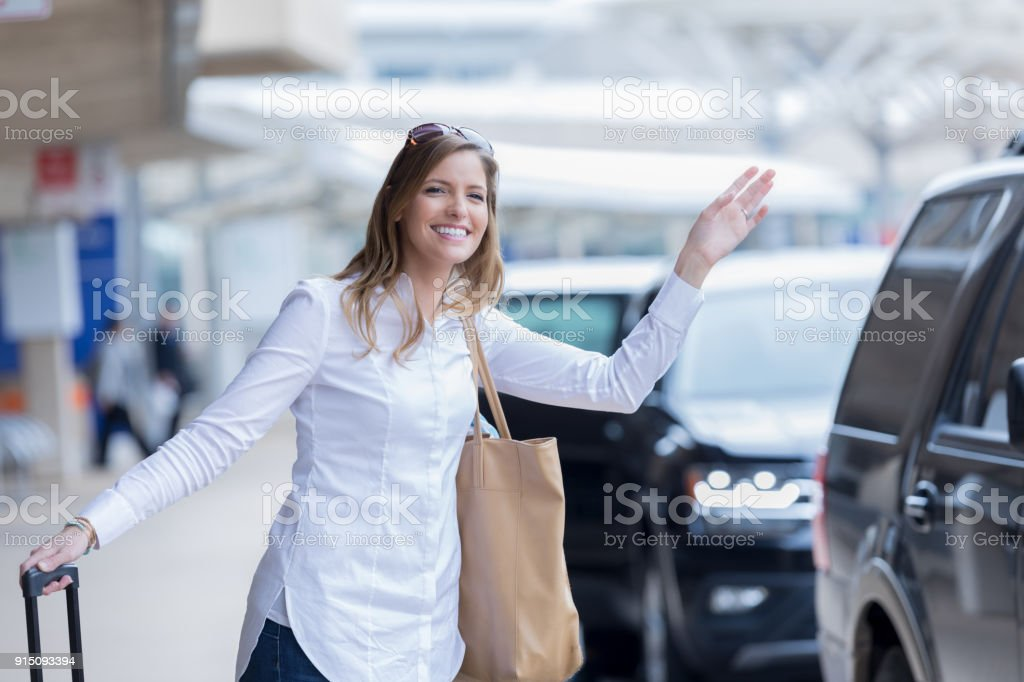 Woman catches friend's attention in airport pickup lane stock photo