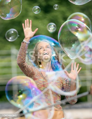 Beautiful natural woman popping soap bubbles with a playful candid lifestyle smile. Nikon D850. Converted from RAW.