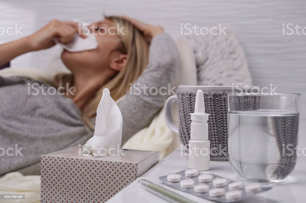 Woman caught cold , frunning nose, selective focus on tissue box. stock photo