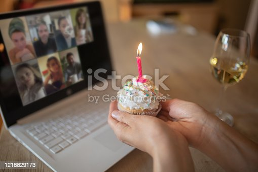 Mature woman celebrating her birthday alone at home but with friends online on video conference. She looks happy and elegant and holding cupcake with candle. She is lonely in quarantine during lockdown because of corona virus outbreak