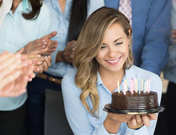 woman celebrating her birthday at the office - super torte stock-fotos und bilder