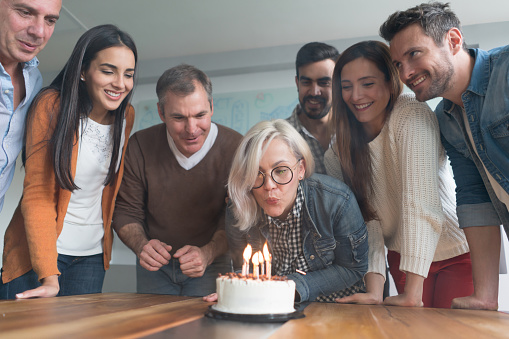 Woman celebrating her birthday at the office with her coworkers and blowing out the candles - team concepts
