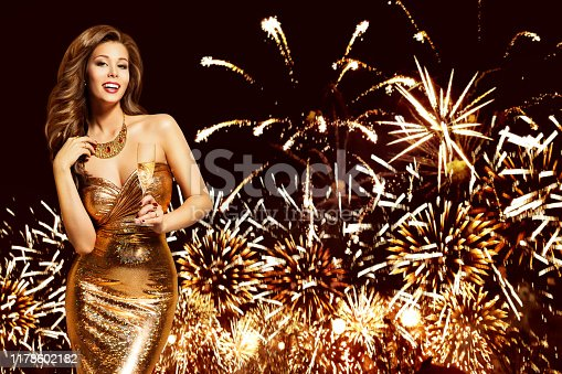 Woman Celebrating New Year Party over Fireworks Night Sky, Elegant Happy Fashion Model in Golden Dress