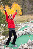 Woman Celebrating on Mini Golf Course