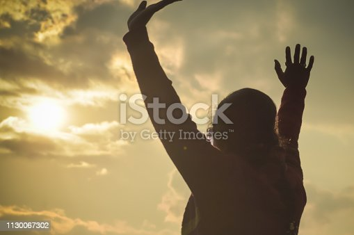Woman celebrating on the top at sunrise. Silhouette adult lady stretching out hands on sunset. Young girl raising hands feel freedom and relaxation travel outdoor enjoying nature. Success concept