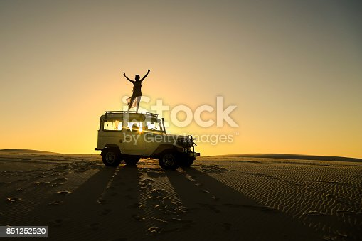istock woman celebrating on top of offroad car 851252520