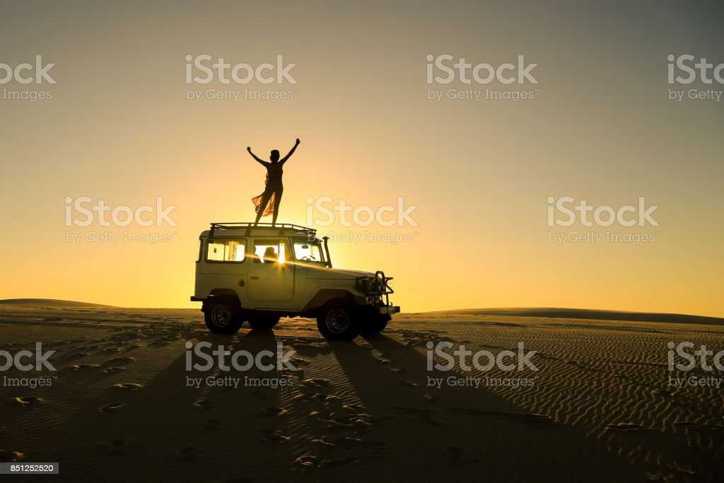 woman celebrating on top of offroad car stock photo