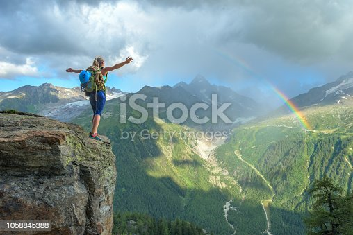 Woman celebrating her success in climbing the mountain in front of a colorful rainbow